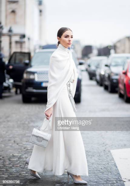Olivia Culpo wearing white Nina Ricci skirt belt and top Ferragamo bag Casadei heels Maria Black jewelery on March 2 2018 in Paris France
