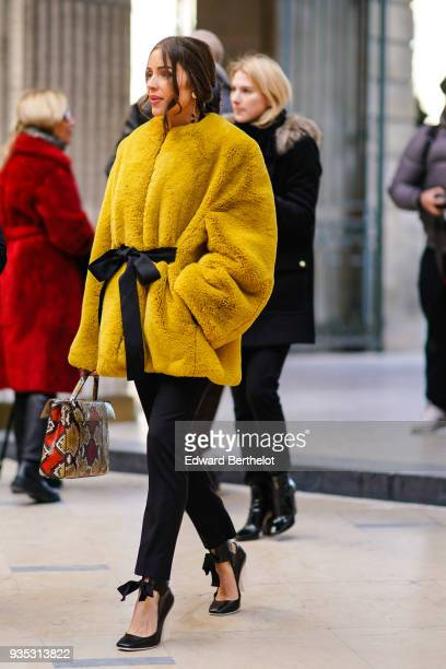 Olivia Culpo wears a black bow in her hair a yellow coat with a black bow belt straight black pants black patent leather highheeeled pumps with white...