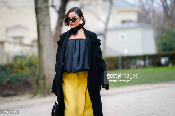 Olivia Culpo wears a black coat a yellow skirt a pleated top black boots a bag during Paris Fashion Week Womenswear Fall/Winter 2018/2019 on February...
