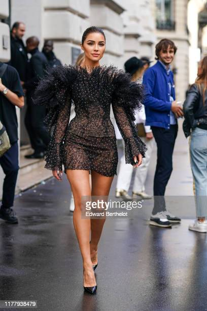 Olivia Culpo wears a black ruffled lace mesh dress, outside Ralph & Russo, during Paris Fashion Week - Womenswear Spring Summer 2020, on September...