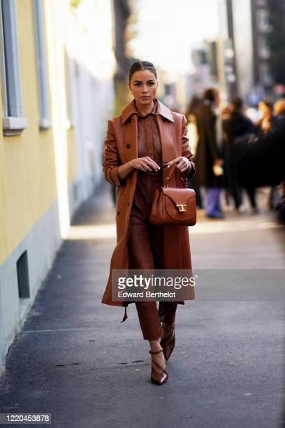 Olivia Culpo wears a brown long leather coat, a brown mesh shirt, leather pants, a brown leather bag, pointy shoes, outside Tod's, during Milan...