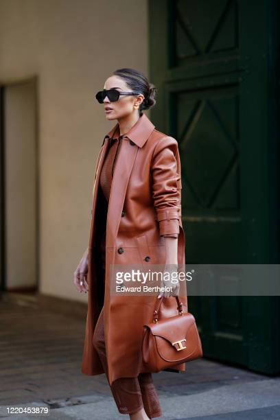 Olivia Culpo wears a brown long leather coat, a brown mesh shirt, leather pants, a brown leather bag, outside Tod's, during Milan Fashion Week...