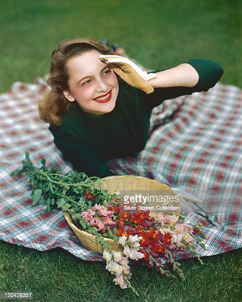 Olivia de Havilland, British actress, wearing a green jumper and gardening gloves she lays on a tartan rug with a basket of snapdragons, circa 1945.