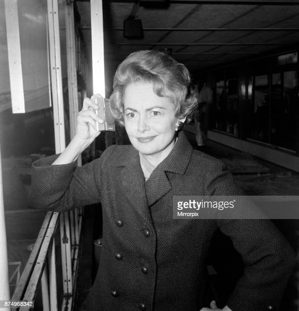 Olivia De Havilland listens to the budget at London Airport while waiting for a flight home to Paris 15th April 1964