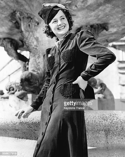 Olivia de Havilland portant un manteau militaire rouge bordeaux circa 1940 à Hollywood Californie