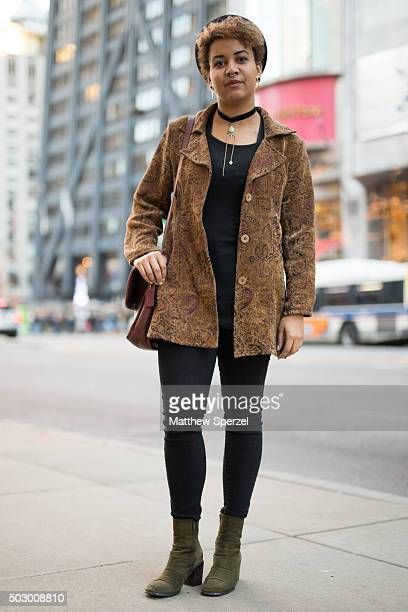 Olivia Engobor is seen on Michigan Avenue wearing black HM hat and shirt brown/gold patterned vintage North Style coat black Forever 21 pants dark...