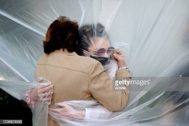 Olivia Grant hugs her grandmother, Mary Grace Sileo through a plastic drop cloth hung up on a homemade clothes line during Memorial Day Weekend on...