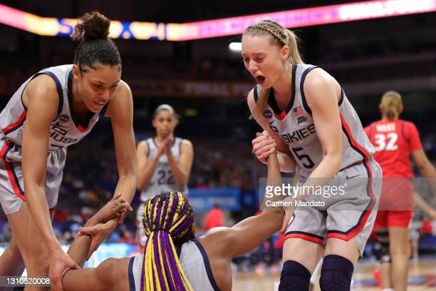 Olivia Nelson-Ododa of the UConn Huskies and Paige Bueckers help up Aaliyah Edwards during the first quarter in the Final Four semifinal game of the...