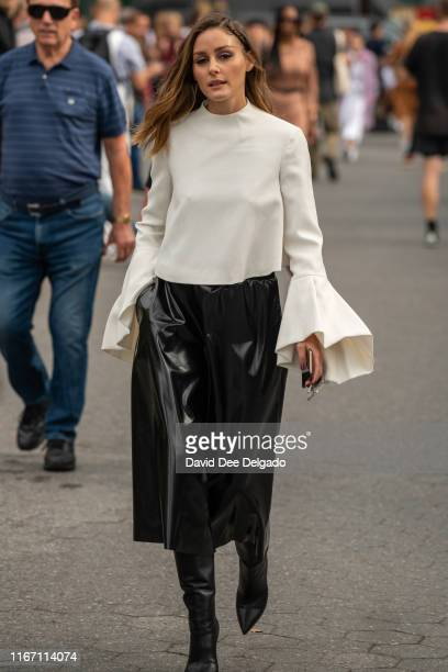 Olivia Palermo is seen wearing a cream blouse a black skirt and black boots during New York Fashion Week at the Garden of the Battery on September 9...