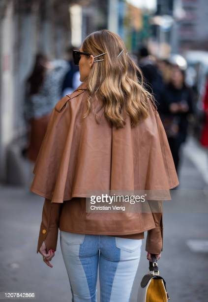 Olivia Palermo is seen wearing two tone denim jeans, brown cape, hair clip outside Tods during Milan Fashion Week Fall/Winter 2020-2021 on February...