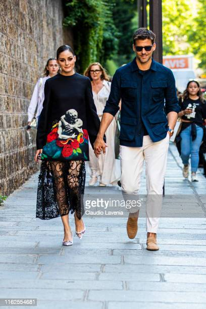Olivia Palermo , wearing a printed decorated top, black lace skirt and pink decorated heels, and Johannes Huebl, wearing a blue shirt, white pants...