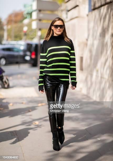 Olivia Palermo wearing black neon striped knit black vinyl pants sunglasses is seen outside Balmain during Paris Fashion Week Womenswear...