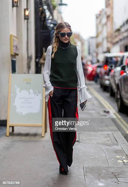 Olivia Palermo wearing sunglasses a green sleeveless jumper white blouse black track suit pants outside Mary Katrantzou during London Fashion Week...