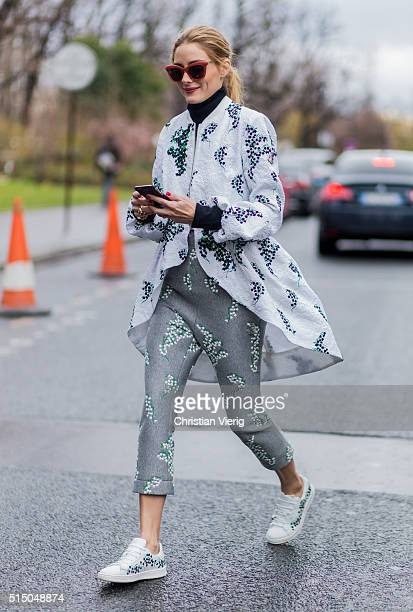 Olivia Palermo wearing total look Moncler Gamme Rouge a white jacket black turtleneck red sunglasses and grey pants and white sneaker outside Moncler...