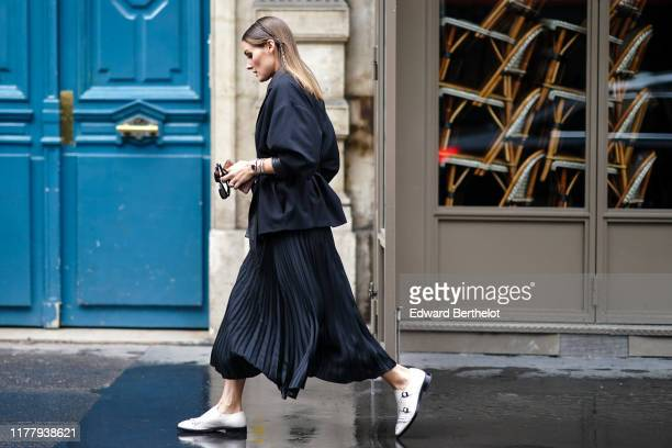 Olivia Palermo wears a balck jacket a black pleated skirt white shoes outside Ralph Russo during Paris Fashion Week Womenswear Spring Summer 2020 on...