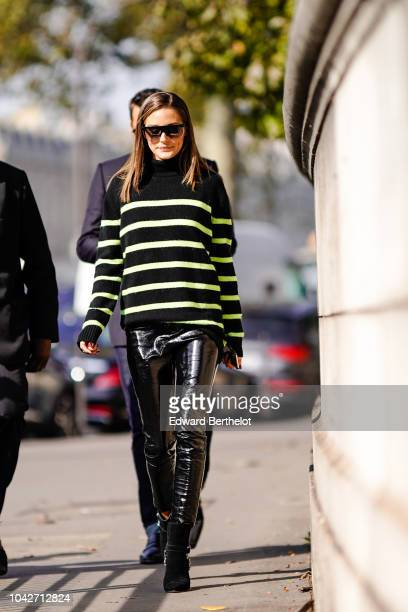 Olivia Palermo wears a black and yellow striped pullover black pvc pants outside Balmain during Paris Fashion Week Womenswear Spring/Summer 2019 on...