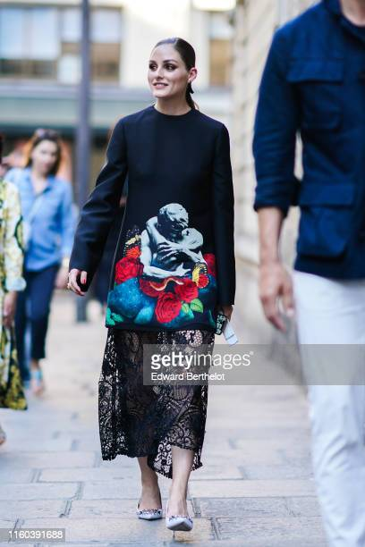 Olivia Palermo wears a black dress with printed multicolor drawing depicting a couple kissing and a black lace mesh embroidered lower part outside...