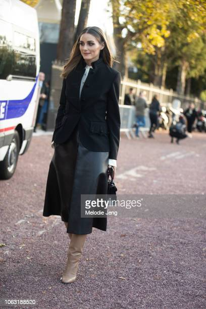 Olivia Palermo wears a black jacket black leather skirt tan leather boots at the Hermes show at the Longchamp Racecourse during Paris Fashion Week...