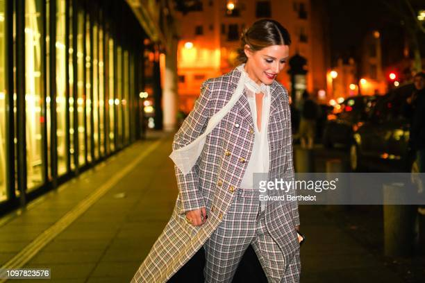 Olivia Palermo wears a checked jacket a white lace scarf flare pants outside Valli during Paris Fashion Week Haute Couture Spring Summer 2020 on...