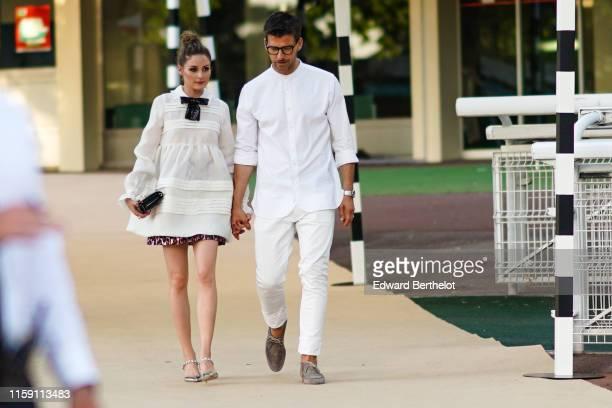 Olivia Palermo wears a white dress and a black sequined bow tie Johannes Huebl wears a white shirt glasses outside Miu Miu Club 2020 on June 29 2019...