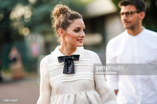 Olivia Palermo wears a white dress and a black sequined bow tie, outside Miu Miu Club 2020, on June 29, 2019 in Paris, France.