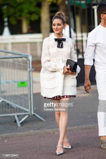 Olivia Palermo wears a white dress and a black sequined bow tie outside Miu Miu Club 2020 on June 29 2019 in Paris France