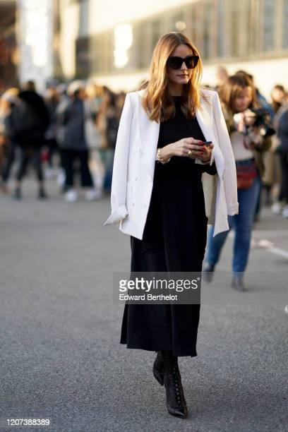 Olivia Palermo wears a white jacket a black dress outside Alberta Ferretti during Milan Fashion Week Fall/Winter 20202021 on February 19 2020 in...