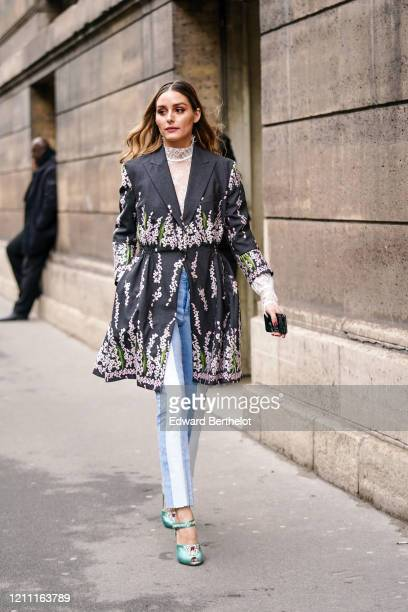 Olivia Palermo wears a white lace hi-neck top, a dark grey coat with pink and green floral embroideries, blue and white ripped hem jeans, nacreous...