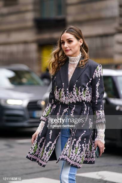 Olivia Palermo wears a white lace hi-neck top, a dark grey coat with pink and green floral embroideries, blue and white jeans, outside Giambattista...