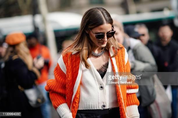 Olivia Palermo wears an orange wool knitted jacket black flared pants sunglasses outside Miu Miu during Paris Fashion Week Womenswear Fall/Winter...