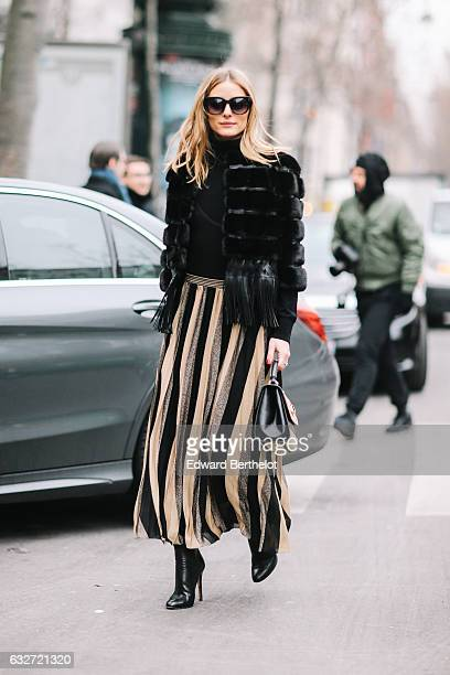 Olivia Palermo wears black sunglasses a black fur coat a striped dress and black heels outside the Elie Saab show during Paris Fashion Week Haute...