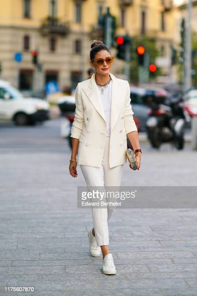Olivia Palermo wears brown sunglasses a white blazer jacket a necklace a white tshirt cropped pants sneakers a golden clutch outside the Alberta...