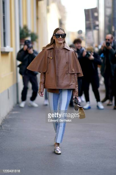 Olivia Palermo wears mirror sunglasses, a brown leather jacket, blue and white striped pants, a bag, silver shiny shoes, outside Tod's, during Milan...