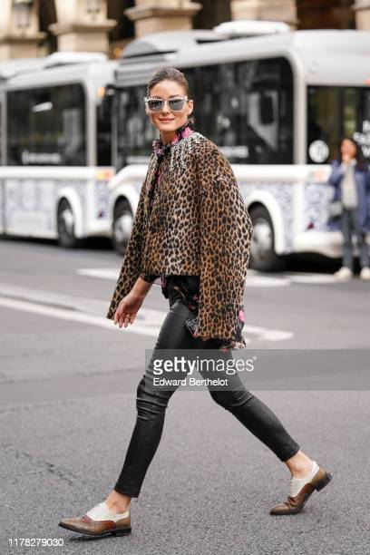 Olivia Palermo wears mirror sunglasses, a leopard print jacket, black leggings, brown leather shoes outside Giambattista Valli, during Paris Fashion...