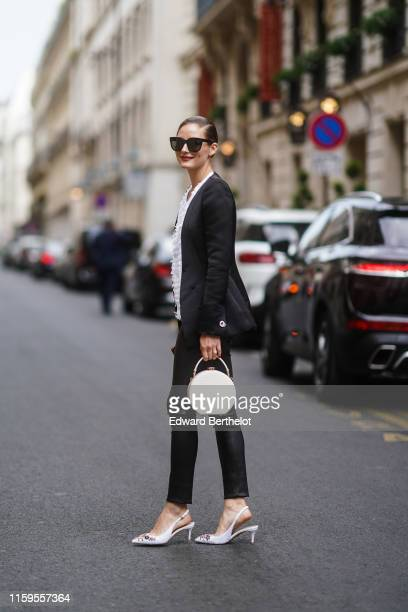 Olivia Palermo wears sunglasses, a black blazer jacket, a white top, black leather pants, shoes, a white circular bag, outside Ralph & Russo, during...