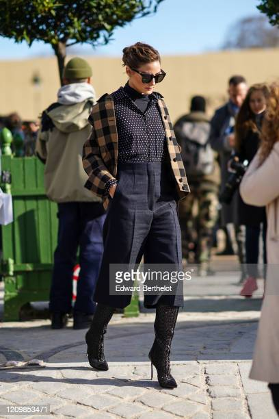 Olivia Palermo wears sunglasses, a brown and black checked pattern jacket, a black shirt with printed white polka dots, a turtleneck top, cropped...