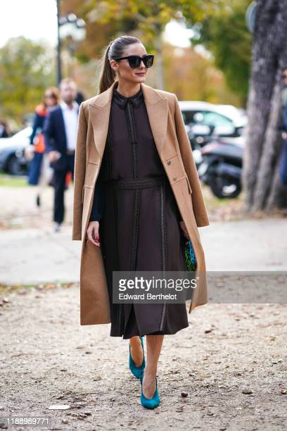 Olivia Palermo wears sunglasses, a camel colored long coat, a brown dress, blue turquoise shoes, outside Elie Saab, during Paris Fashion Week -...