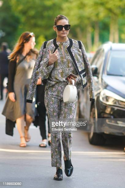 Olivia Palermo wears sunglasses a floral print jacket top pants black shoes a white circular bag outside Giambattista Valli during Paris Fashion Week...