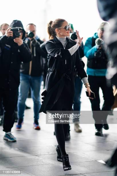 Olivia Palermo wears sunglasses, a grey turtleneck, a navy blue ruffled dress, black ankle boots, outside Giambattista Valli, during Paris Fashion...