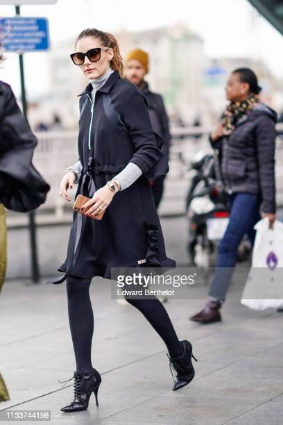 """Olivia Palermo wears sunglasses, a grey turtleneck, a navy blue ruffled dress with the inscription """"I love Giamba"""" at the hem , black ankle boots,..."""