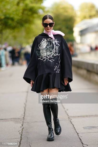 Olivia Palermo wears sunglasses, a pink scarf, a black sweater with printed flower and chains, a black pleated ruffled skirt, black leather high...