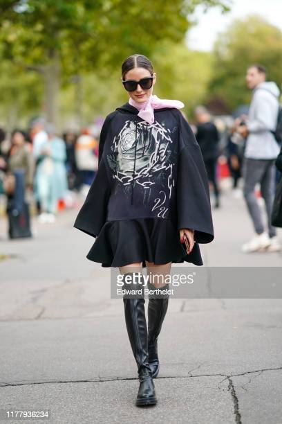 Olivia Palermo wears sunglasses a pink scarf a black sweater with printed flower and chains a black pleated ruffled skirt black leather high boots...