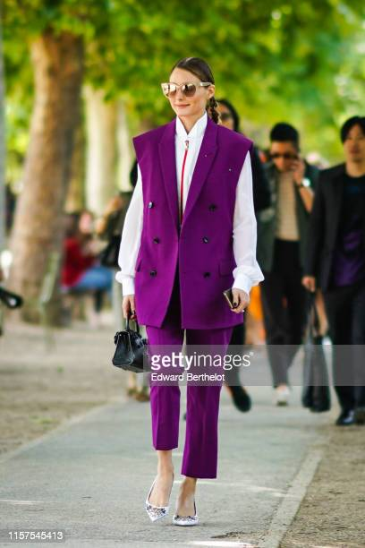 Olivia Palermo wears sunglasses, a purple sleeveless blazer jacket, a white shirt, purple pants, outside Berluti, during Paris Fashion Week -...
