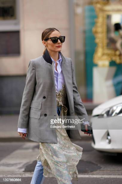 Olivia Palermo wears sunglasses, a purple/white striped shirt, a gray oversized blazer jacket, blue and white striped pants, a lace floral print...