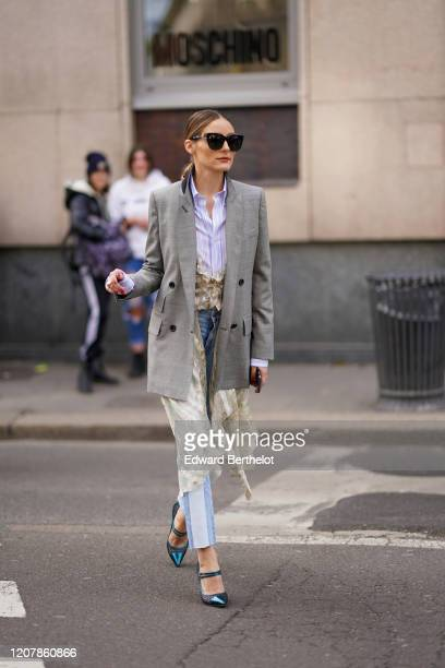 Olivia Palermo wears sunglasses, a purple/white striped shirt, a gray oversized blazer jacket, blue and white striped pants, green shoes, a lace...