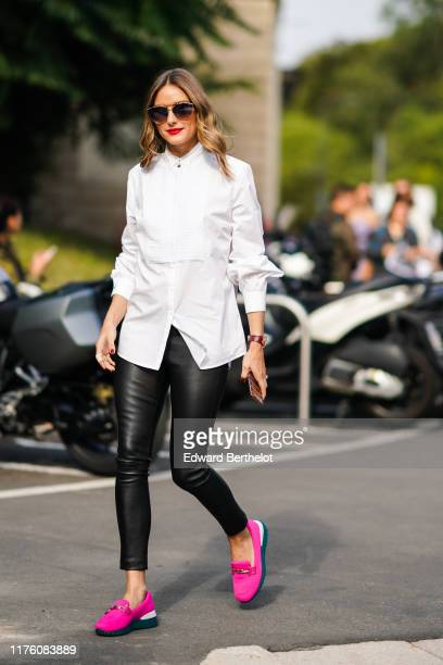 Olivia Palermo wears sunglasses, a white shirt, black leather pants, pink shoes, outside the Tod's show during Milan Fashion Week Spring/Summer 2020...