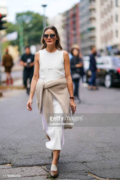 Olivia Palermo wears sunglasses a white sleeveless dress a pullover around the waist a watch leather brown and white shoes outside the Sportmax show...