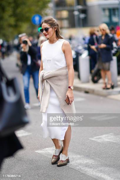 Olivia Palermo wears sunglasses, a white sleeveless dress, a pullover around the waist, a watch, leather brown and white shoes, outside the Sportmax...