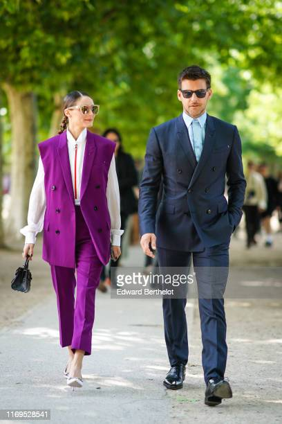 Olivia Palermo wears sunglasses, a white wing collar shirt with a red zip, an oversized cyclamen-color vest, cyclamen-color pants, a black leather...