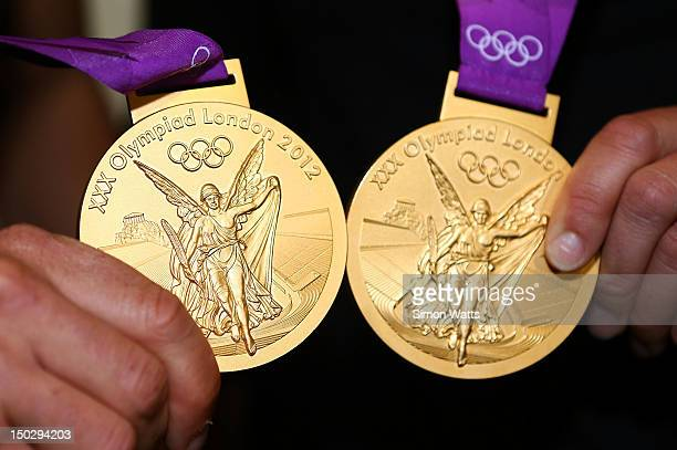 Olivia Powrie and Jo Aleh of the New Zealand Olympic team display their Gold Medals after arriving at Auckland International Airport after competing...